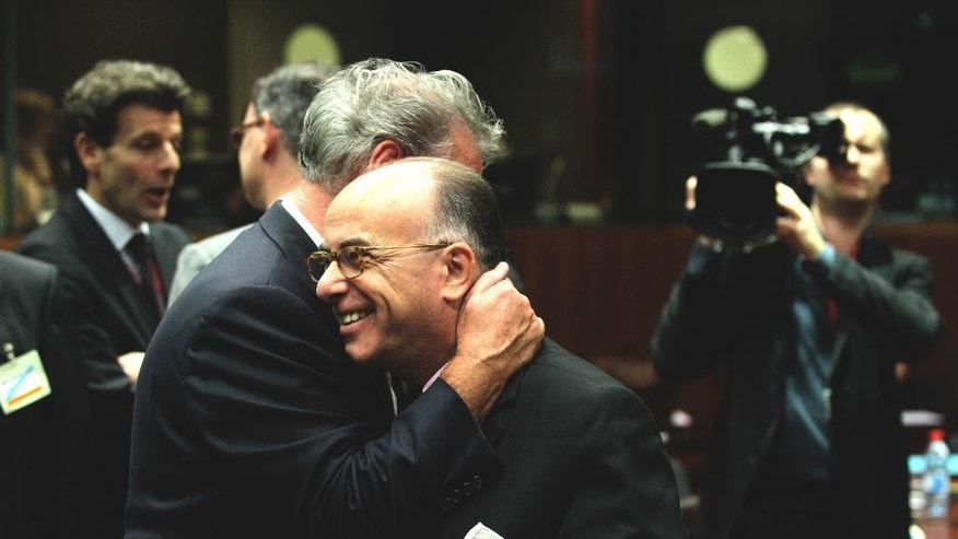 French Interior minister Bernard Cazeneuve, right,  is hugged by Luxembourg Foreign and European Minister  Jean Asselborn during a round table meeting of EU justice and interior ministers at the EU Council building in Brussels on Monday, Nov. 9, 2015. EU justice and interior ministers met Monday to discuss the ongoing crisis of migrants and refugees. (AP Photo/Francois Walschaerts)