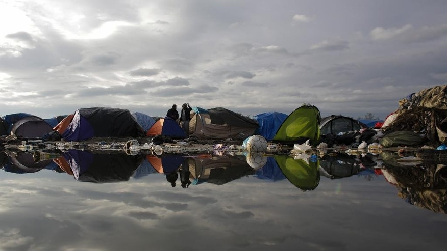 In this Tuesday, Nov. 3, 2015, file photo, tents and waste are reflected in a puddle inside the migrants camp near Calais, northern France. Residents of France's biggest refugee camp near the English Channel port of Calais must combat hunger, filth and illness in a tent village as they scramble to build hard roofs for the winter.  (AP Photo/Markus Schreiber)