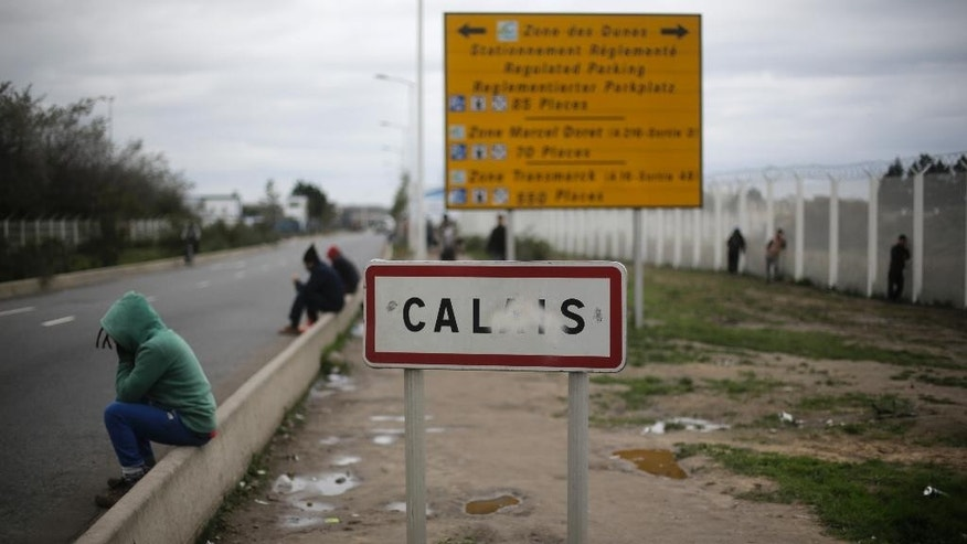 In this Thursday, Nov. 5, 2015 photo, migrants gather at the city sign of Calais near the migrants camp near Calais, northern France. (AP Photo/Markus Schreiber)