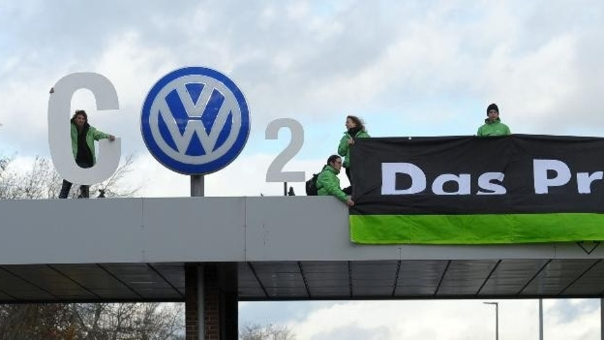 Greenpeace activists stand with 'CO2' formed with the VW logo and a banner that reads 'the problem' above the Volkswagen factory gate in Wolfsburg, Germany, Monday, Nov. 9, 2015. (Peter Steffen/dpa via AP)