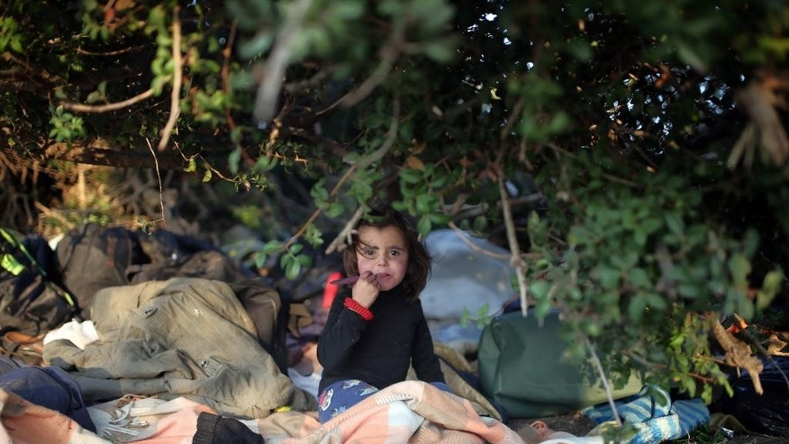 In this late Saturday, Nov. 7, 2015 photo made available Sunday, a young migrant waits with her family members to travel by dinghies to the Greek islands from Turkish coast near Bodrum, Turkey.  More than 300,000 people have traveled on boats from nearby Turkey to Greek islands this year, with uncounted numbers dying along the way. (AP Photo/Emre Tazegul)