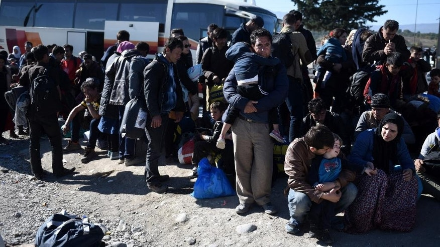 People wait in a queue to be allowed to pass from the northern Greek village of Idomeni to southern Macedonia, Monday, Nov. 9, 2015. Well over half a million migrants have arrived in Greece from Turkey and the vast majority don't want to stay so head north through the Balkans to other, more prosperous European Union countries. (AP Photo/Giannis Papanikos)