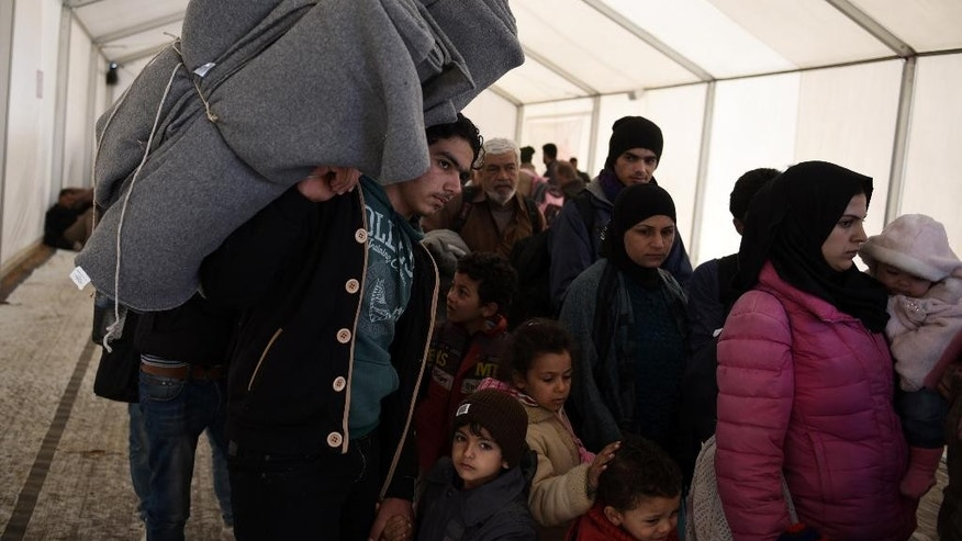 Migrants and refugees wait in a queue inside a large tent, to be allowed to pass from the northern Greek village of Idomeni to southern Macedonia, Monday, Nov. 9, 2015. Well over half a million migrants have arrived in Greece from Turkey and the vast majority don't want to stay so head north through the Balkans to other, more prosperous European Union countries. (AP Photo/Giannis Papanikos)
