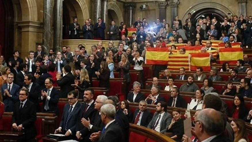 Popular Party of Catalonia members show Spanish flags and Catalonia flags at the end of a parliamentary session Monday.