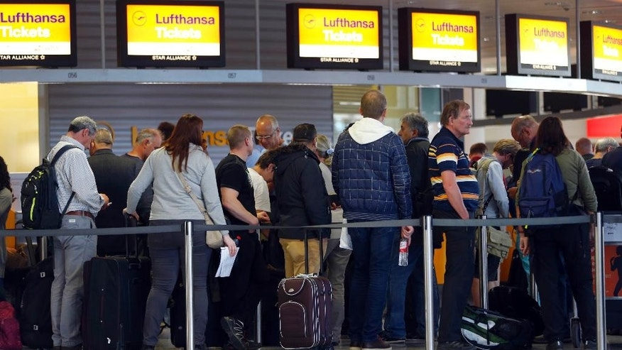 Passengers wait for information at a Lufthansa counter at the airport in Munich, Germany, Monday, Nov. 9, 2015. Germany's biggest airline, Lufthansa, canceled 600 flights on Monday in Munich as cabin crew workers went on strike. (AP Photo/Matthias Schrader)