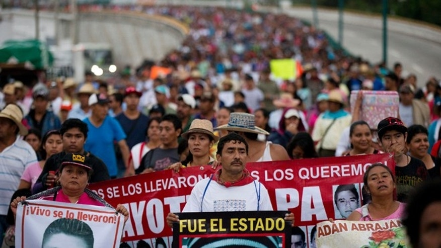 FILE - In this Saturday, Sept. 26, 2015, file photo, relatives of the 43 missing Ayotzinapa teachers' college students lead a march marking the one-year anniversary of the students' disappearances in Chilpancingo, Mexico. In a document released Sunday, Nov. 8, 2015, Mexico's National Human Rights Commission is criticizing the Attorney General's Office for failing to address all the recommendations it made in July about the investigation into the fate of 43 missing college students. (AP Photo/Rebecca Blackwell, File)