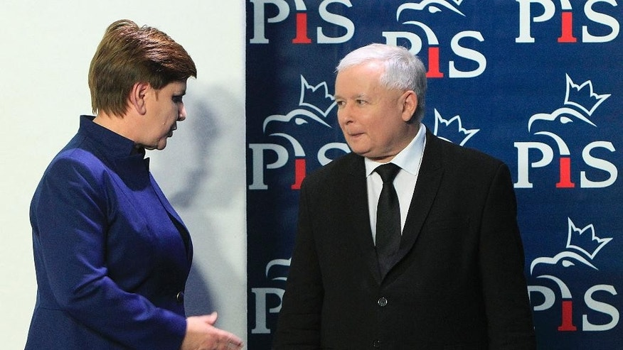 Jaroslaw Kaczynski, right, the leader of the conservative Law and Justice party, PiS, talks with designated prime minister Beata Szydlo after she announced members of her new cabinet in Warsaw, Poland, Monday, Nov. 9, 2015. (AP Photo/Czarek Sokolowski)