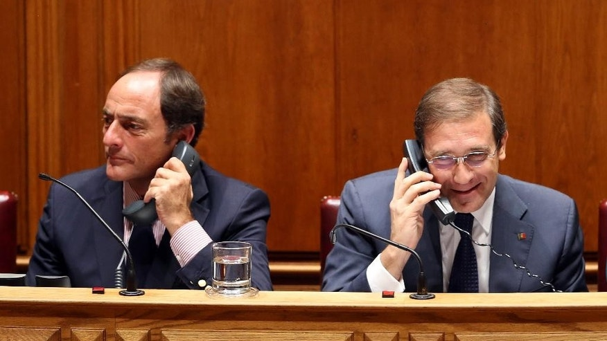 Portuguese Prime Minister Pedro Passos Coelho, right, and Deputy Prime Minister Paulo Portas use telephones during the debate of the government's four-year policy program at the Parliament in Lisbon, Monday, Nov. 9 2015. Together the left-of-center parties have 122 seats in the 230-seat Parliament, outnumbering the government, and have vowed to reject the program in a vote expected Tuesday. Such a defeat would force the government, which took office on Oct. 30, to resign, possibly opening the door for the unprecedented leftist alliance to take over. (AP Photo/Armando Franca)