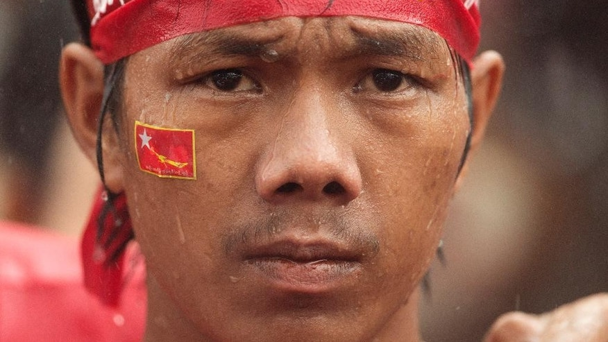 A supporter of of Myanmar's National League for Democracy party, waits in pouring rain outside the NLD headquarters in Yangon, Myanmar, Monday, Nov. 9, 2015. Opposition leader Aung San Suu Kyi's party was confident Monday that it was headed for a landslide victory in Myanmar's historic elections, as the democracy icon urged supporters not to provoke losing rivals who mostly represent the former junta that ruled this Southeast Asian nation for a half-century. (AP Photo/Mark Baker)