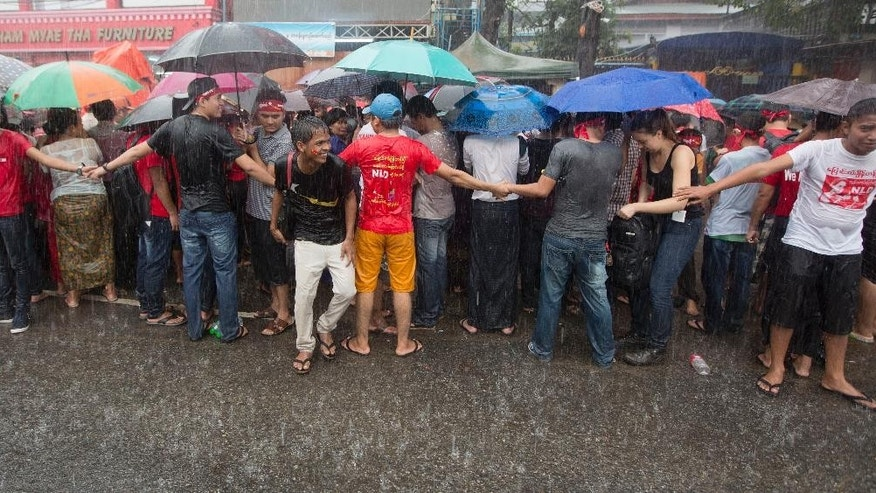 Supporters of of Myanmar's National League for Democracy party, wait in pouring rain outside the NLD headquarters in Yangon, Myanmar, Monday, Nov. 9, 2015. With tremendous excitement and hope, millions of citizens voted Sunday, Nov. 8 in Myanmar's historic general election that will test whether the military's long-standing grip on power can be loosened, with opposition leader Aung San Suu Kyi's party expected to secure an easy victory.(AP Photo/Mark Baker)