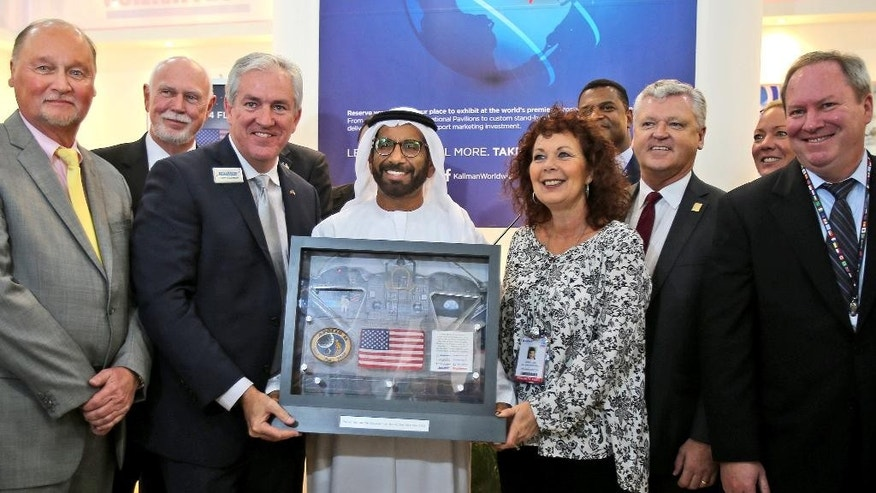 Khalifa Mohammed Al Rumaithi, Chairman of the UAE Space Agency, center, receives a United States of America flag and other memorabilia from the 1971 Apollo 14 lunar mission from Kallman Worldwide during the third day of the Dubai Airshow in the United Arab Emirates, Tuesday, Nov. 10, 2015. (AP Photo/Kamran Jebreili)