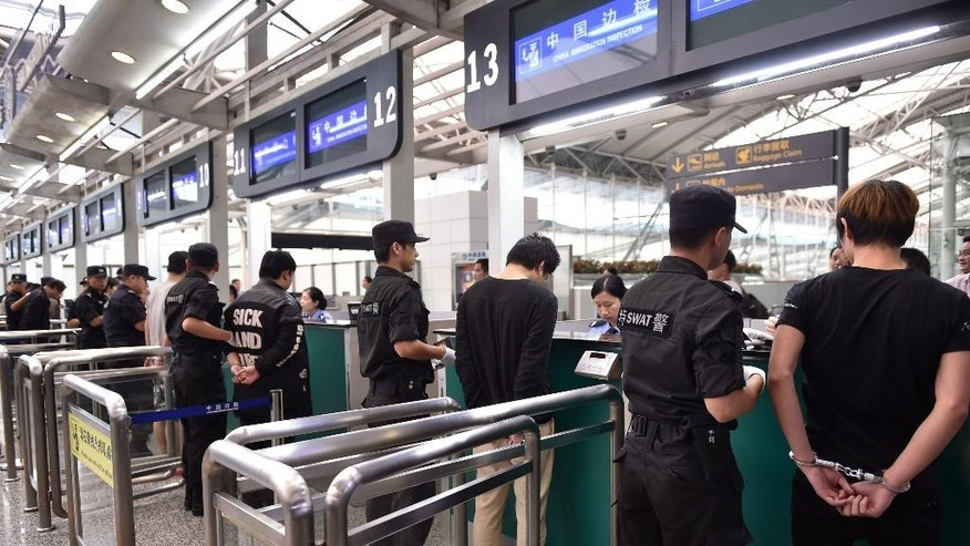 In this photo released by China's Xinhua News Agency, suspects are escorted to go through Customs by police officers at Guangzhou Baiyun International Airport in Guangzhou, capital of south China's Guangdong Province, Tuesday, Nov. 10, 2015. Over 200 Chinese citizens arrested in Cambodia and Indonesia for running telephone scams targeting Chinese victims were repatriated Tuesday to face charges in China, the Public Security Ministry said. A statement on the ministry's website said the suspects were flown back to Beijing and three other Chinese cities aboard chartered flights. They are suspected of committing upward of 4,000 major cases of cross-border telephone fraud targeting victims in more than 20 cities and provinces, the ministry said. (Liang Xu/Xinhua via AP) NO SALES