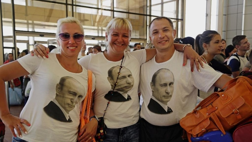FILE-- In this Friday, Nov. 6, 2015 file photo, Russian tourists wearing t-shirts with images of Russian President Vladimir Putin pose for a photo in the departure terminal before boarding a flight from Sharm el-Sheikh, south Sinai, Egypt. Egypt's benchmark stock index plunged 4.4 percent on Tuesday, Nov. 10, 2015, after steadily declining since Russia suspended flights to Egypt following the Oct. 31 Russian plane crash in the Sinai Peninsula. (AP Photo/Thomas Hartwell, File)