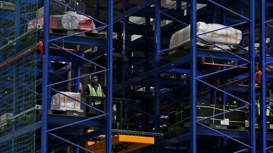 An employee of Emirates SkyCentral uploads goods at their facilities of the Al Maktoum International Airport in Dubai, United Arab Emirates, Monday, Nov. 9, 2015. Emirates, the Mideast's top airline, has expanded its cargo operation out to Dubai's new airport as it looks toward the future. (AP Photo/Kamran Jebreili)
