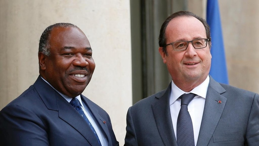 French President Francois Hollande, right, poses with Gabon's President Ali Bongo Ondimba, upon arrivals at the Elysee Palace for a meeting as part of preparation of the upcoming COP21 Climate Conference in Paris, France, Tuesday, Nov. 10, 2015. (AP Photo/Francois Mori)