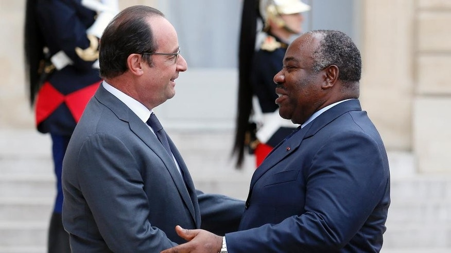 French President Francois Hollande, left, welcomes Gabon's President Ali Bongo Ondimba, upon arrivals at the Elysee Palace for a meeting as part of preparation of the upcoming COP21 Climate Conference in Paris, France, Tuesday, Nov. 10, 2015. (AP Photo/Francois Mori)