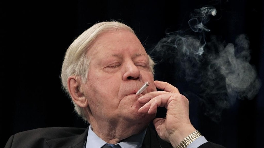 FILE - In this April 2, 2009 file photo former German Chancellor Helmut Schmidt smokes a cigarette during a discussion hosted by the ECB in Frankfurt, central Germany. Helmut Schmidt died Nov. 10, 2015. He was 96. (AP Photo/Daniel Roland, file)