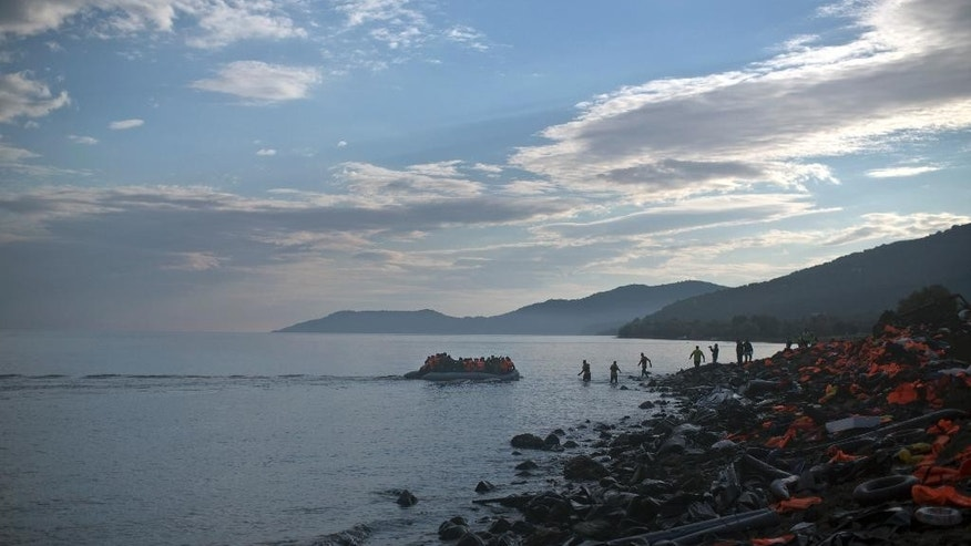 A boat carrying migrants and refugees arrives at a beach on the northern shore of Lesbos, Greece, Tuesday, Nov. 10, 2015. Well over half a million people have reached the Greek islands so far this year, a record number of arrivals, and the journey has proved fatal for hundreds. (AP Photo/Marko Drobnjakovic)