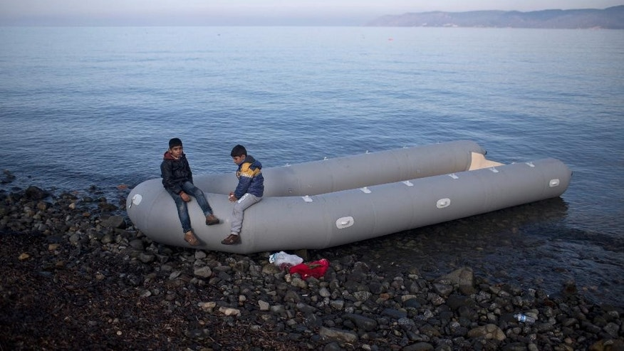 Two boys sit on an inflatable dinghy after arriving from neighboring Turkey at a beach on the northern shore of Lesbos, Greece, Tuesday, Nov. 10, 2015. Over half a million migrants and refugees have reached the Greek islands so far this year, a record number of arrivals, and the journey has proved fatal for hundreds. (AP Photo/Marko Drobnjakovic)