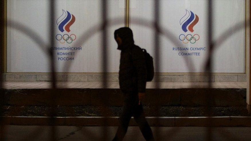 A man walks by the Russian Olympic committee building in Moscow, Russia, Monday, Nov. 9, 2015. Russian track and field athletes could be banned from next year's Olympics in Rio de Janeiro after a devastatingly critical report accused the country's government of complicity in widespread doping and cover-ups. (AP Photo/Ivan Sekretarev)