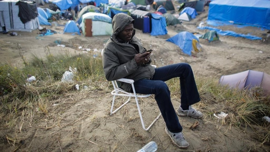 In this Thursday, Nov. 5, 2015 photo a man communicates with his smart phone as he sits on a chair inside the migrant camp near Calais, northern France.  (AP Photo/Markus Schreiber)