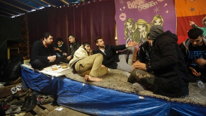 In this Friday, Nov. 6, 2015 photo male migrants sits inside a makeshift Afghan restaurant at the migrants camp in Calais, northern France. More than 5000 migrants are fleeing conflict zones or poverty at the rapidly growing camp known locally as 'The Jungle', outside Calais.  (AP Photo/Markus Schreiber)