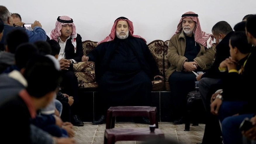 Suleiman Saed, center, a relative of Anwar Abu Zaid, the alleged shooter who opened fire Monday, Nov. 9, 2015 on instructors at an international police training center in Jordan's capital, killing at least five people, including two Americans, briefs the media at the family home in Amman, Jordan, Tuesday, Nov. 10, 2015. Saed is a former member of parliament and speaks on behalf of the family. Jordan has not released the name of the attacker, but Saed says he was told by security officials that Abu Zaid was the attacker. (AP Photo/Raad Adayleh)