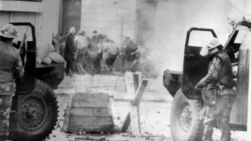 """Soldiers take cover behind armored cars on """"Bloody Sunday"""" in 1972."""