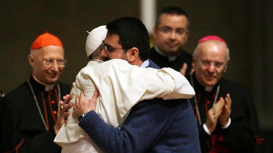 Pope Francis is hugged by a priest in the Cathedral Santa Maria del Fiore during his visit to Florence, Italy, Tuesday, Nov. 10, 2015. (AP Photo/Gregorio Borgia)