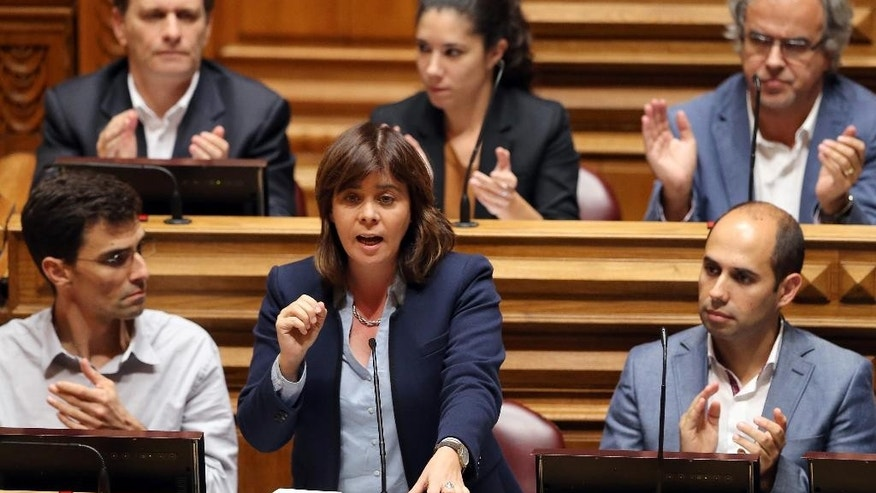 Catarina Martins, center, leader of the Left Bloc, is applauded during the debate of the government's four-year policy program at the Parliament in Lisbon, Monday, Nov. 9 2015. Together the left-of-center parties have 122 seats in the 230-seat Parliament, outnumbering the government, and have vowed to reject the program in a vote expected Tuesday. Such a defeat would force the government, which took office on Oct. 30, to resign, possibly opening the door for the unprecedented leftist alliance, that includes the Left Bloc, to take over. (AP Photo/Armando Franca)