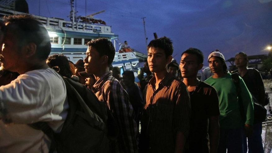 In this April 3, 2015, file photo, Burmese fishermen prepare to board a boat during a rescue operation in Benjina, Aru Islands, Indonesia. Thai police on Tuesday, Nov. 10, 2015, announced the arrest of a man they said tricked more than 100 men into working for low pay on illegal fishing boats in Indonesia, part of the government's effort to show that it is cracking down on an industry that has been rife with human trafficking and labor abuses. (AP Photo/Dita Alangkara, File)