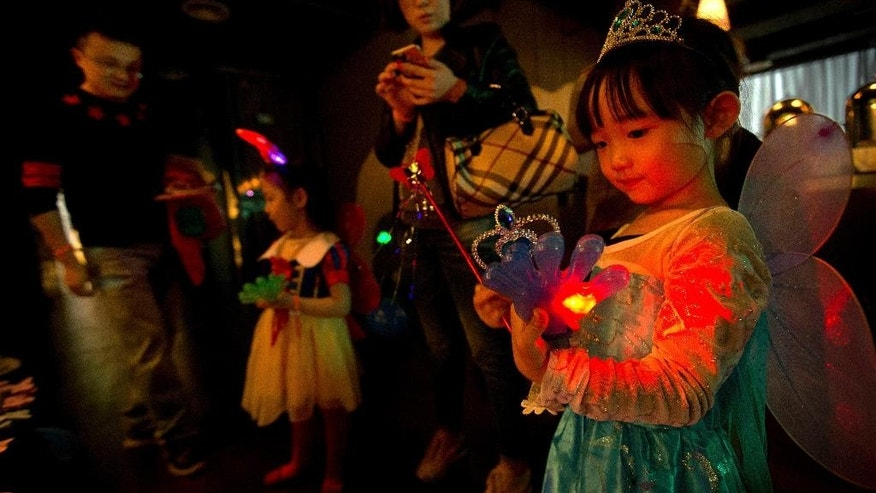 FILE - In this May 10, 2015, file photo, a girl plays with an electronic toy while standing with her family at a Mother's Day-themed disco dance party for children in Beijing. Chinese authorities expect that easing the country's one-child policy will add more than 30 million people to the country's labor force by 2050, a senior official said Tuesday, Nov. 10, 2015. (AP Photo/Mark Schiefelbein, File)