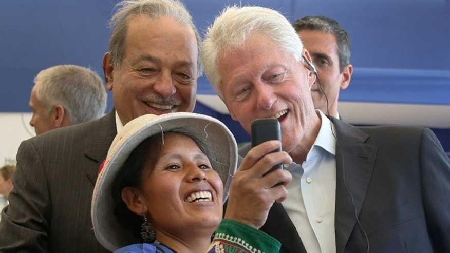 An Andean woman takes a photo of herself with former President Bill Clinton, right, and Mexico's billionaire Carlos Slim, during their visit to the San Juan de Lurigancho district of Lima, Peru, Wednesday, Nov. 11, 2015, where the Clinton Foundation runs a program that helps women set up small businesses. Clinton began a tour of Latin America, including El Salvador and Panama, where his foundation also runs programs to aid farmers and women. (AP Photo/Martin Mejia)