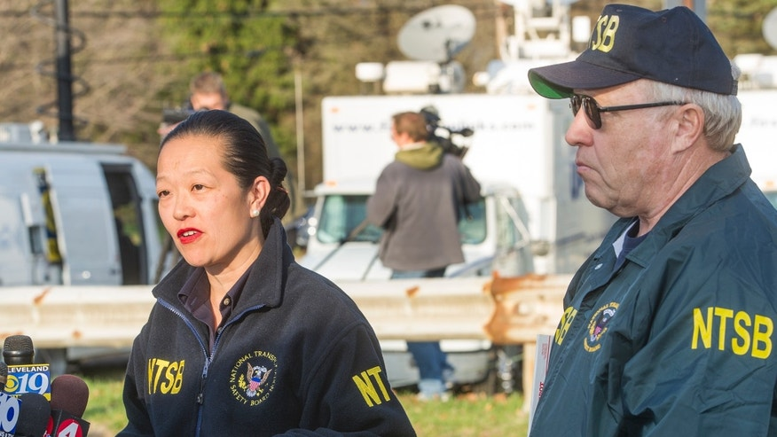 Bella Dinh-Carr, vice-chairman of the National Transportation Safety Board, speaks to reporters at a news conference, as NTSB lead investigator, Jim Silliman watches, Wednesday, Nov. 11, 2015, in Akron, Ohio. Dint-Carr is explaining the status of the NTSB investigation into yesterday's jet plane crash in Akron that killed nine people, seven passengers and two pilots, as the plane was attempting to land at Akron Fulton Airport.  No one on the ground was injured or killed. (AP Photo/Phil Long)