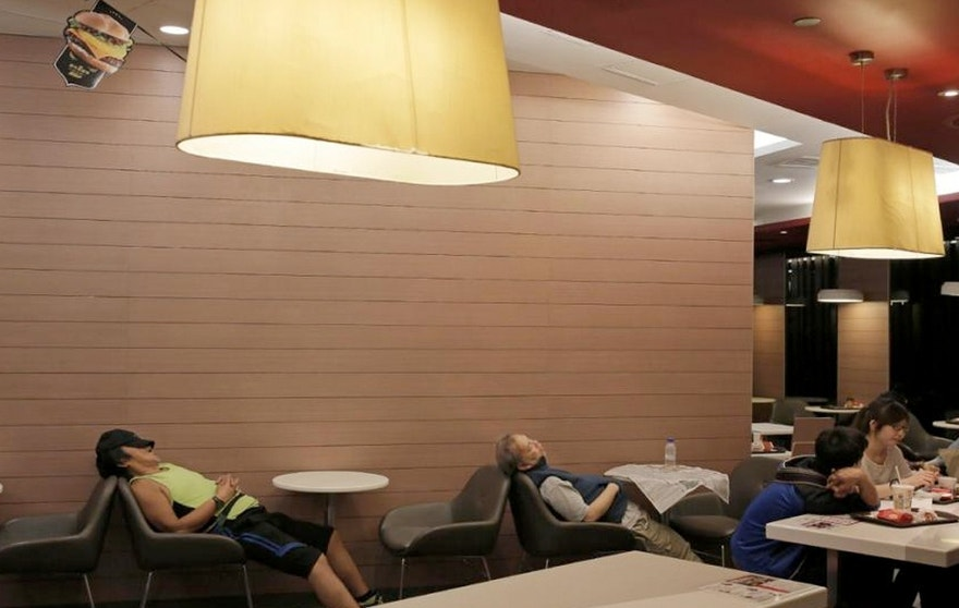 Two men sleep at night in a 24-hour McDonald's branch in Hong Kong.