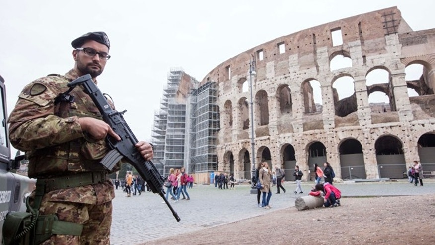 Soldiers patrol in front of the Colosseum in Rome, Saturday, Nov. 14, 2015. Italy's top security official says Italy has heightened security inside Italy and along its borders, especially with France, following the attacks in Paris. Interior Minister Angelino Alfano said that 700 soldiers were being deployed immediately to Rome as a deterrent and additional security measures will be taken into consideration for the upcoming Jubilee year declared by Pope Francis that is expected to bring millions to Rome beginning Dec. 8. (AP Photo/Riccardo De Luca)
