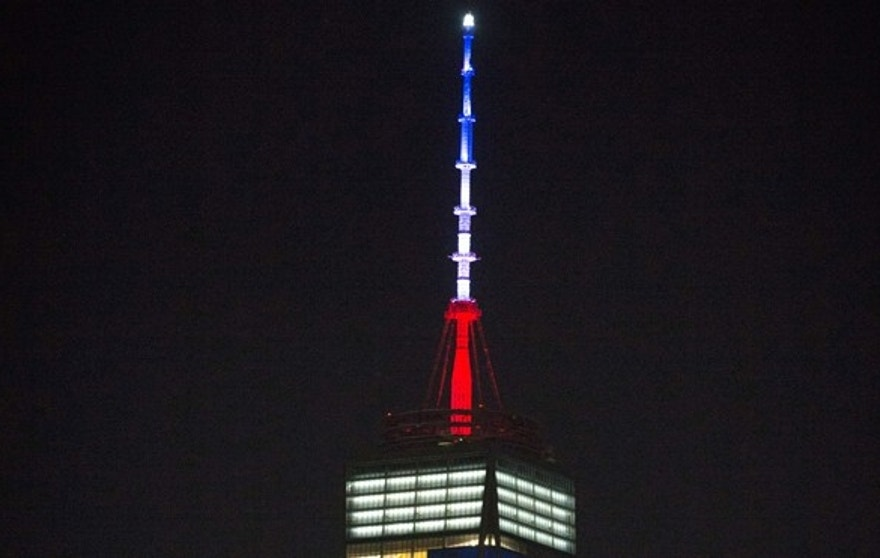 The One World Trade Center spire is lit blue, white and red after New York Gov. Andrew Cuomo announced the lighting in honor of dozens killed in the Paris attacks.