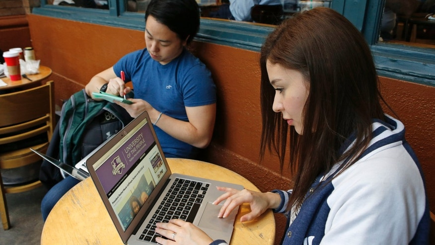 Colombian-born immigrant Nathaly Ordonez, 23, browses the tuition-free, online University of the People's home page, Thursday, Nov. 5, 2015, in New York, while looking at her next semester's classes and studying with boyfriend Shota Hanawka.   Ordonez, had nearly abandoned the idea of college because it was too expensive, but is now studying business so she can work in advertising when she graduates. (AP Photo/Kathy Willens)