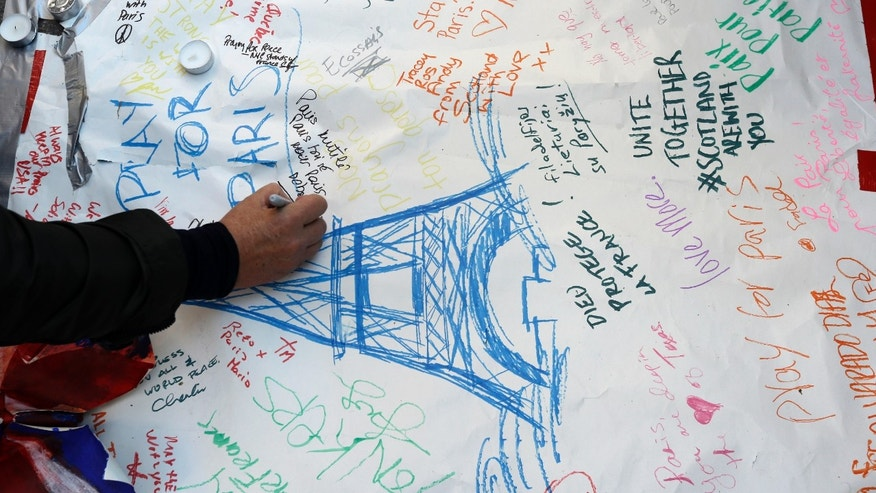 A mourner signs a makeshift memorial for the victim of the attacks in Paris in New York's Washington Square park, Saturday, Nov. 14, 2015. Multiple attacks across Paris on Friday night have left scores dead and hundreds injured. (AP Photo/Mary Altaffer)