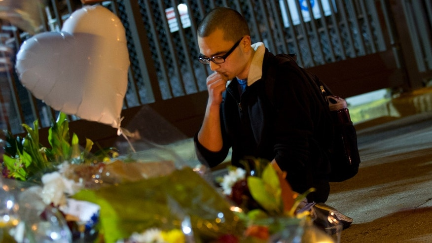 A person pauses after placing flowers outside the gates of the French Embassy in Washington, Saturday, Nov. 14, 2015, following deadly attacks in Paris on Friday. (AP Photo/Jose Luis Magana)
