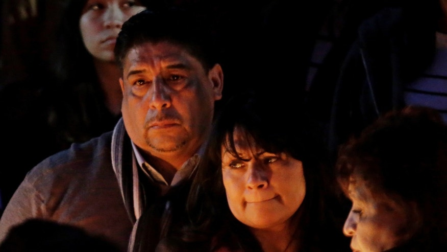 Beatrez Gonzalez, center, mother of California State Long Beach student Nohemi Gonzalez holds up candle with her step-father Jose Hernandez, left, during a memorial service on Sunday, Nov. 15, 2015 in Long Beach, Calif., for Gonzalez who was killed at restaurant in Paris on Friday night during the terrorist attacks. (AP Photo/Chris Carlson)