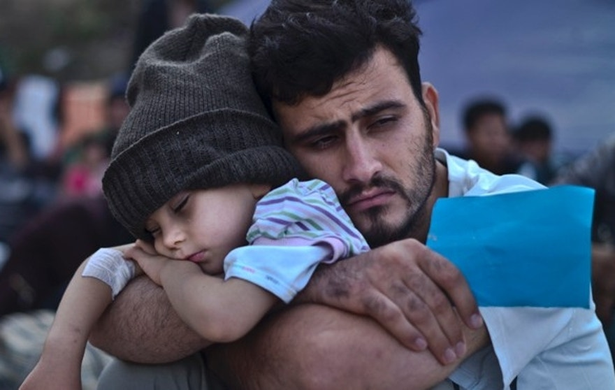FILE - In this Sunday, Oct. 4, 2015 file photo, a Syrian refugee child sleeps in his father's arms while waiting at a resting point to board a bus, after arriving on a dinghy from the Turkish coast to the northeastern Greek island of Lesbos. Bold ideas for helping Syrian refugees and their overburdened Middle Eastern host countries are gaining traction among international donors who were shocked into action by this year's migration of hundreds of thousands of desperate Syrians to Europe. (AP Photo/Muhammed Muheisen, File)