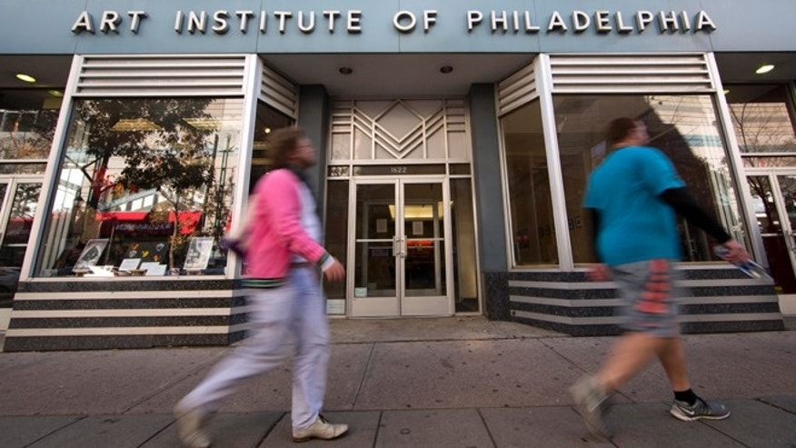 People walk past the Art Institute of Philadelphia operated by the Education Management Corporation on Monday, Nov. 16, 2015, in Philadelphia. The Obama administration has reached a $95.5 million settlement with a Pittsburgh firm that runs for-profit trade schools and colleges. The Justice Department settlement resolves allegations that Education Management Corporation used enrollment incentives to pay its recruiters and exaggerated its career-placement ability. (AP Photo/Matt Rourke)