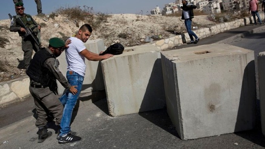 Israeli border police search a Palestinian, next to newly placed concrete blocks in an east Jerusalem neighborhood, last month. (AP Photo/Oded Balilty)