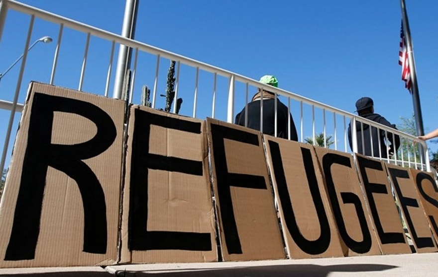 A sign welcoming Syrian refugees is placed at the entrance to the office of the Arizona governor during a rally at the Arizona Capitol.