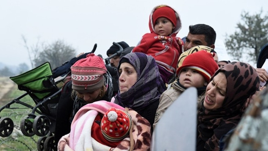 Refugees wait to be allowed to cross from the northern Greek village of Idomeni to southern Macedonia, on Friday, Nov. 20, 2015. The United Nations refugee agency says Macedonia has begun allowing only people from Syria, Iraq and Afghanistan to cross its southern border from Greece, while Greek authorities say migrants of other nationalities are gathering on the Greek side of the border and blocking the crossing completely. (AP Photo/Giannis Papanikos)