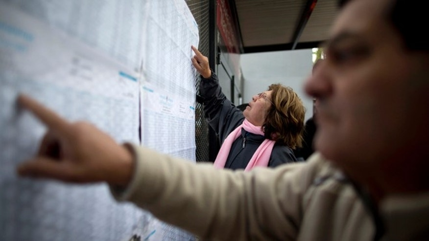 People look for their names on voter lists during elections in Buenos Aires, Argentina, Sunday, Oct. 25, 2015. Argentines are weighing continuity versus a financial overhaul in Sunday's elections as they pick the successor to President Cristina Fernández, a polarizing leader who dominated national politics for 12 years. (AP Photo/Natacha Pisarenko)