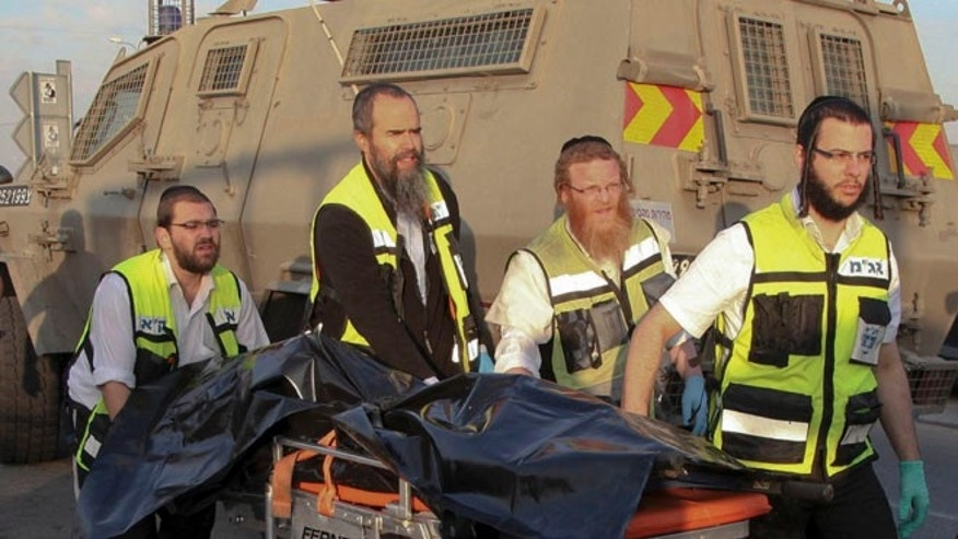 Israeli emergency services evacuate the body of a Palestinian from the scene of an attack near the West Bank Gush Etzion settlements.