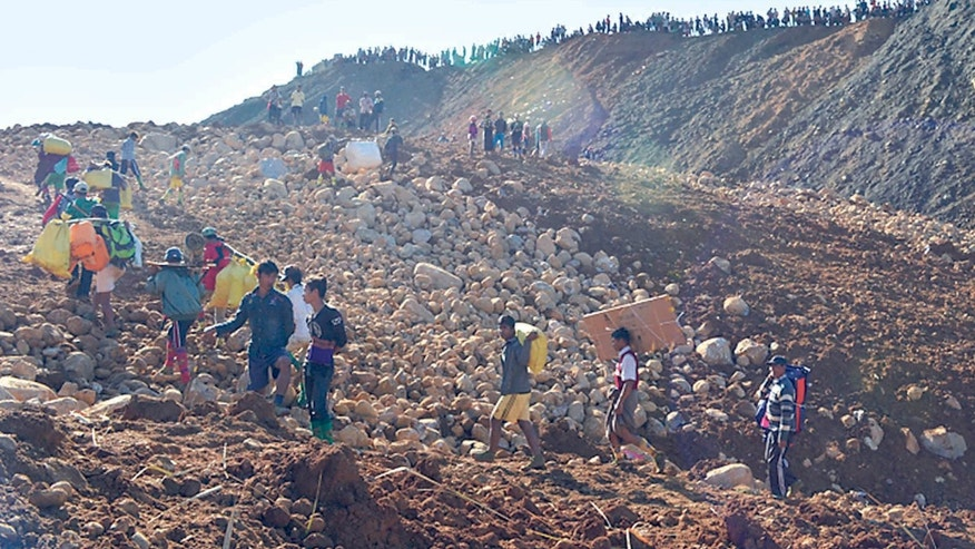 Nov. 21, 2015: Mine workers carrying their belongings walk after their houses were destroyed by a landslide in Phakant jade mine, Kachin State, Myanmar.