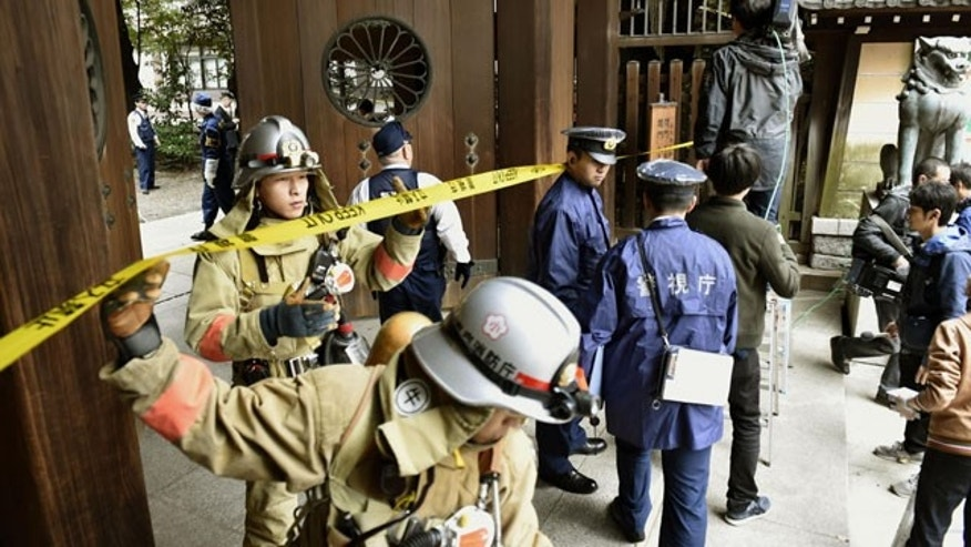 Nov. 23, 2015: Firefighters and police officers inspect around the south gate of Yasukuni shrine in Tokyo after an explosion was reported.  No one was injured.  (Shigeyuki Inakuma/Kyodo News via AP)